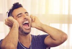 Exuberant mens die aan zijn muziek luisteren Stock Afbeeldingen