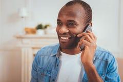 Exuberant mens die op de telefoon spreken stock afbeelding
