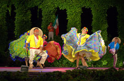 Exuberant Mexican dance. Mexican folkloric ballerinas dressed  in colorful costumes  and male spirited dance performance blindfold machete dancers Royalty Free Stock Image