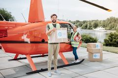 Exuberant two volunteers embarking boxes. Quick help. Pleasant two volunteers loading cases and standing near helicopter royalty free stock image