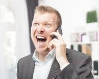 Exuberant young man shouting in reaction to a call. Exuberant young man in a suit jacket and open neck shirt shouting in reaction to a call on his mobile phone Royalty Free Stock Image