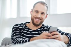 Exuberant young man typing on his phone Stock Images