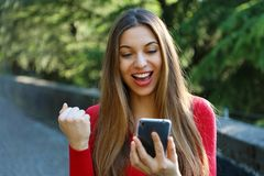 Exuberant young woman cheering at good news on her mobile phone and punching the air with her fist.  royalty free stock photos