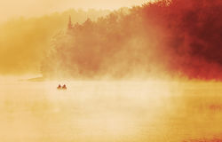 Exuding fishermen fishing in a lake, early misty foggy morning s Royalty Free Stock Image