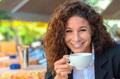Exultant young woman enjoying a cup of coffee Stock Photos