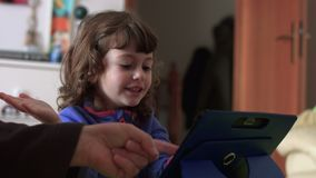 Exulting candid child playing on a tablet close shot SF. Close shot of an Exulting candid child while is playing on a tablet and joking with her father stock footage