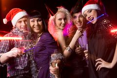 Exulting friends. Company of friends clubbing at disco with flutes of champagne in hands Stock Photos