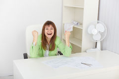 Exulting young woman at office on workplace Stock Photo