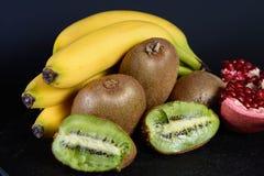 Exxposition de kiwi, de banane et de moitié organiques frais de grenat sur le baground noir, fruit frais, nourriture pour bonjour Images stock