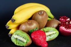 Exxposition del kiwi, della fragola, della banana e della metà organici freschi di granato su baground nero, frutta fresca, alime Immagini Stock