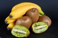 Exxposition del kiwi, della fragola, della banana e della metà organici freschi di granato su baground nero, frutta fresca, alime Fotografie Stock