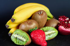 Exxposition do quivi, da morango, da banana e da metade orgânicos frescos da grandada no baground preto, fruto fresco, alimento p Imagens de Stock