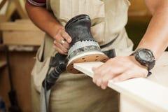 Exzenterschleifmaschine macht das hölzernes Polieren von der Stangenplanke Lizenzfreies Stockfoto