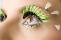 The eye. Detail of an eye with green artificial eyelashes Royalty Free Stock Photo