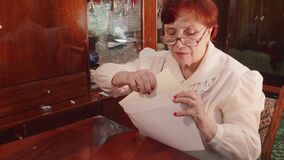 Eye angle view of old woman with glases and red hair who puts folded sheet of paper into envelope. She smiles and talks.