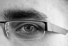 Eye behind glasses. Monochrome image of a man's eye and glasses stock photos