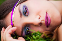 The eye of the beholder. Beautiful brunette model resting in the green grass of the park wearing a purple and gold headband with bright brown eyes staring back Royalty Free Stock Images