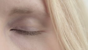 Eye of blonde girl changes color. Close up stock footage