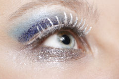 Eye with blue and silver sparkle make-up. One female eye with blue eyeshadow and silver sparkle make-up Royalty Free Stock Images