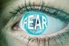 Eye with blue text FEAR. Closeup of the eye of a woman with text FEAR royalty free stock photos