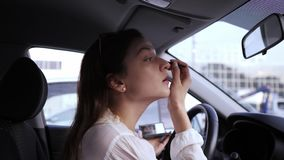 Eye brush, shadows, make-up in the car. A young woman looks in the mirror inside the car and applies make-up before a