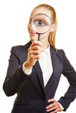 Eye of businesswoman through magnifying glass Royalty Free Stock Photo