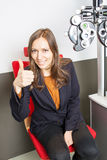 Eye care professional. Woman during an eye exam with thumb up Stock Photography