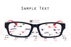 Eye care specs and chart. Black and red reading glasses kept over black and red eye chart with copyspace for text Royalty Free Stock Photos