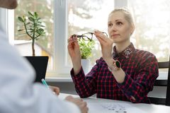 Eye care - woman testing her new eyeglasses in optometrist office stock photography