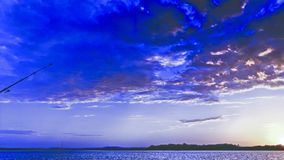 Blue coloured cumulus cloud, sunset seascape vista. An eye catching inspirational blue skyscape sunset wih predominantly cumulus cloud, in a cobalt blue royalty free stock image