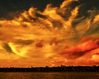 Orange colored stratocumulus cloud, sunset seascape. A eye catching inspirational orange yellow and red coloured stratocumulus cloud, tropical sunset seascape stock photo