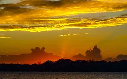 Yellow colored stratus cloud, sunset seascape. A eye catching inspirational yellow and crimson stratus and cumulus cloud in a grey coloured sky. Vibrant sunset stock images