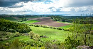 View on landscape with green grass,  hills and trees, cloudy sky royalty free stock photography