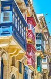 The eye catching Maltese balconies in Valletta. The eye catching wooden Maltese balconies, decorated with bright colors and reliefs, St Paul street, Valletta Royalty Free Stock Images