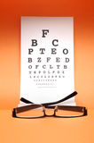 Eye chart test. Eye glass with test chart on orange background Royalty Free Stock Images