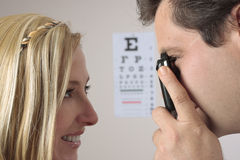 Eye Checkup. Closeup of a an optometrist eye doctor checking a female patient eyes.  Focus to man Stock Photography
