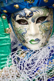 Eye contact. A venetian women wearing a mask with waves and net over the costume