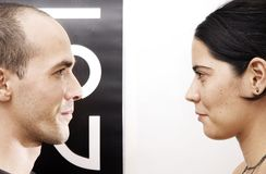 Eye contact - opposites. Portrait of a young couple face to face over back and white background royalty free stock photos