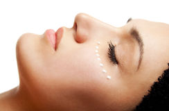 Eye cream treatment. Close-up of beautiful woman face receiving an eye cream treatment Stock Image