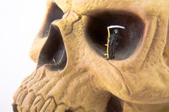 Eye of Death. Miniature grim reaper in eye socket of skull Stock Photography