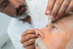 Eye while doctor applying eye drop. Eye stock photos