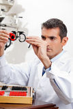 Eye Doctor Checking Lens Of Trial Frames. Optometrist checking the lens of trial frames with concentration for eye examination Royalty Free Stock Images