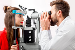 Eye doctor checking vision. Of young female patient with ophthalmologic device in the cabinet Royalty Free Stock Image