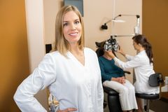 Eye Doctor With Colleague Examining Patient. Portrait of mid adult female eye doctor with colleague examining patient in background Royalty Free Stock Photo
