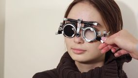 Ophthalmologist is trying on lenses in a trial frame on face of woman. Eye doctor is inserting and taking out testing lenses for correcting vision. Female stock video footage