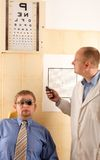 Eye doctor performing eye examination Stock Photo