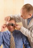 Eye doctor performing eye examination Stock Photos