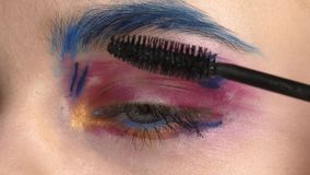 Eye down make-up woman applying eyeshadow, making. Eye down make up woman applying eyeshadow, making exotic, using a special brush, one eye, blue eyebrow, white stock footage