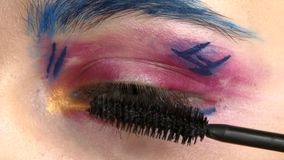 Eye down make-up woman applying eyeshadow, making. Eye down make up woman applying eyeshadow, making exotic, using a special brush, one eye, blue eyebrow, white stock video
