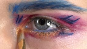 Eye down make-up woman applying eyeshadow, making. Eye down make up woman applying eyeshadow, making exotic, using a special brush, one eye, blue eyebrow, white stock video footage